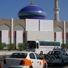 An Orange And White Taxi In Front Of A Mosque In Ruwi